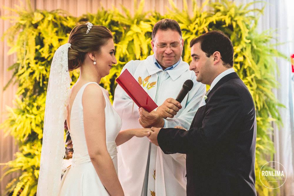 noivo coloca alianças na noiva