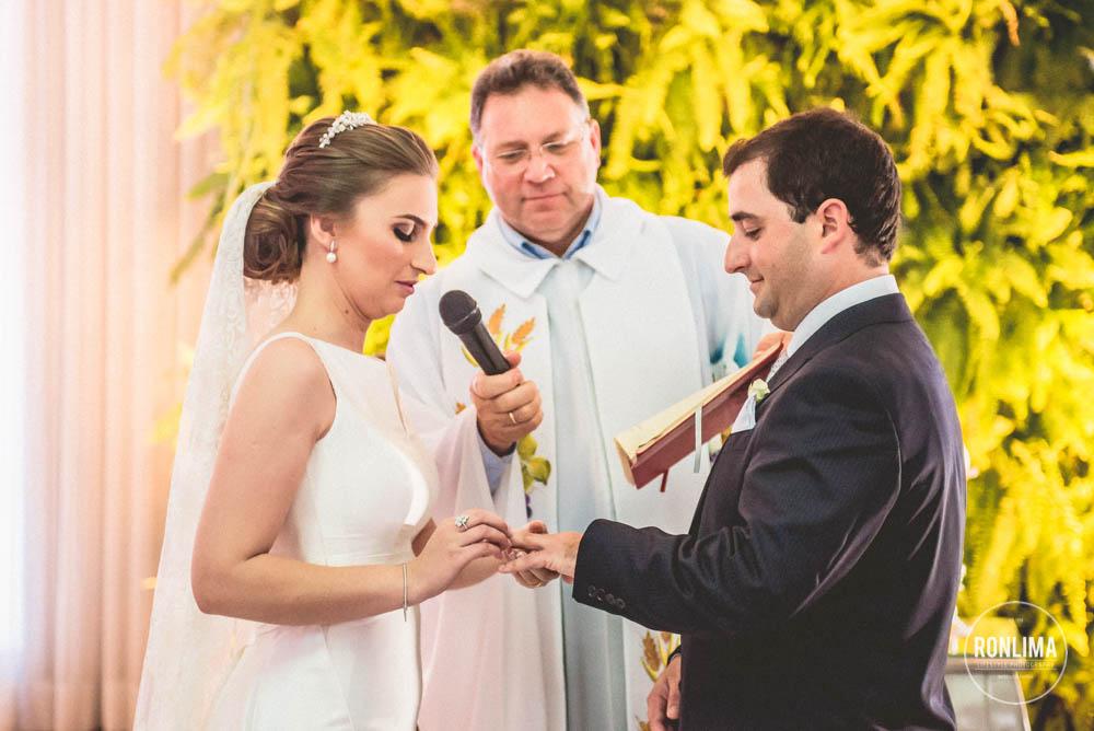 noiva coloca alianças no noivo no casamento